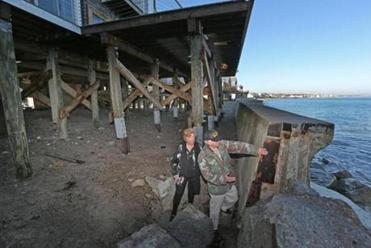 Doris Crary, a Scituate homeowner, looked at a sea wall that collapsed in a recent storm with her husband, Dennis Badore. Four out of six properties she owns were hit last year with $600 to $900 increases in annual insurance premiums.